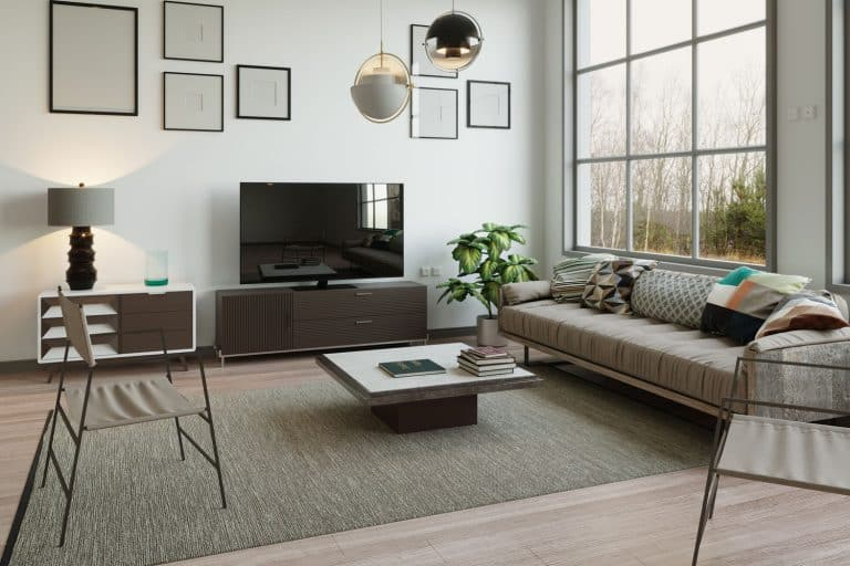 Interior of an ultra modern contemporary living rom with a carpet and a table on the center, How To Float Furniture In A Living Room