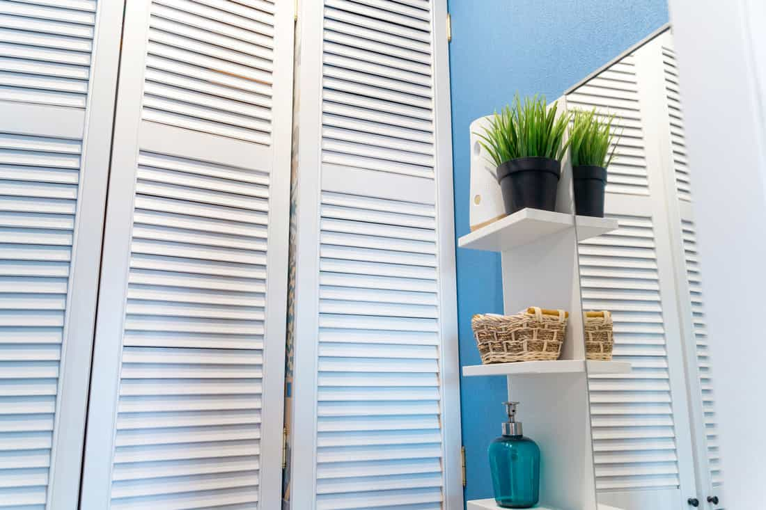Louvered doors in the closet in the toilet, blue walls and a mirror . How To Install A Louvered Door In 6 Easy Steps