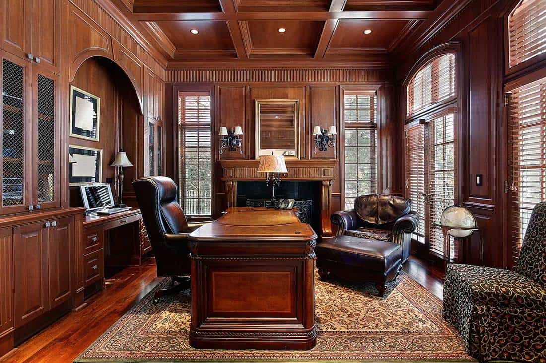 Luxury home office interior with fireplace, wooden furniture and leather chairs