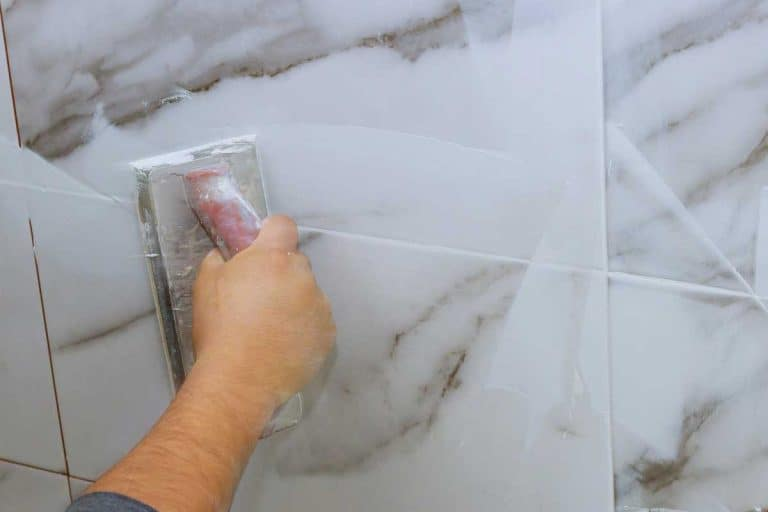 Male hand with the rubber applies grout on a seam between tiles, How Long Does Bathroom Grout Last?