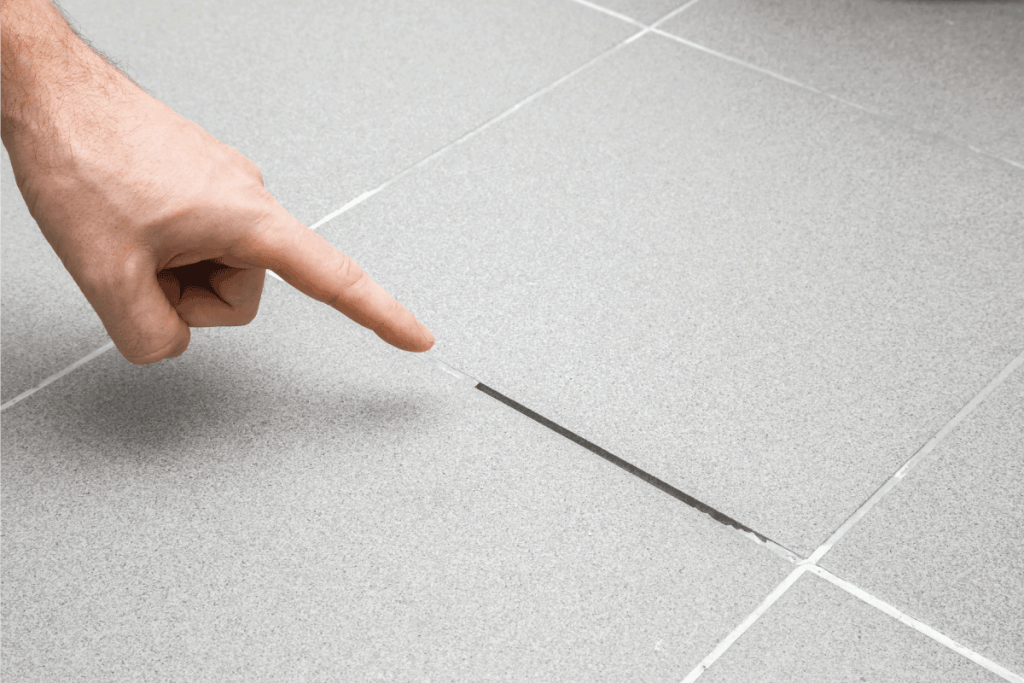 Man's hand finger pointing to space between tiles. Damaged tiles seam. Bathroom Grout Is Falling Out - What To Do About It