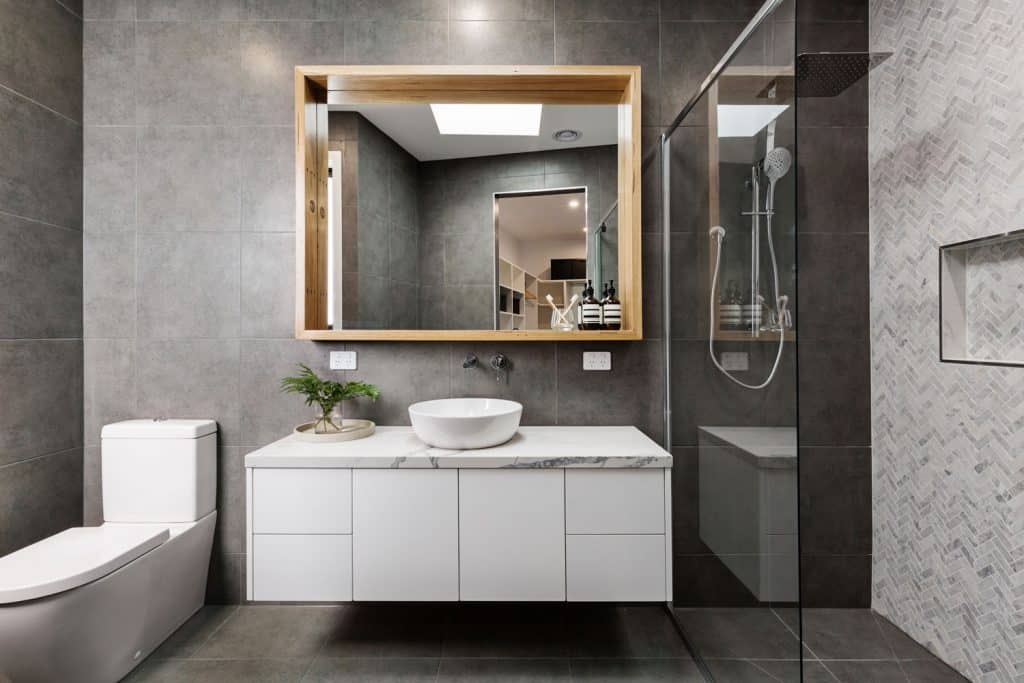 Minimalist inspired bathroom vanity with white colored cabinets and a huge mirror on the side
