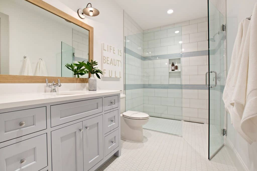 Modern interior of a light retro inspired bathroom with a white mirror, light gray painted cabinetry, and a glass walled shower area