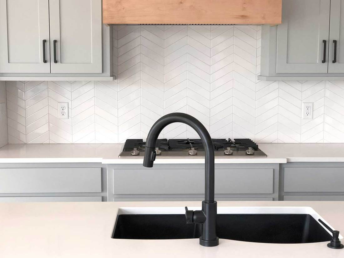 Modern kitchen interior with tiled backsplash and sink on kitchen island
