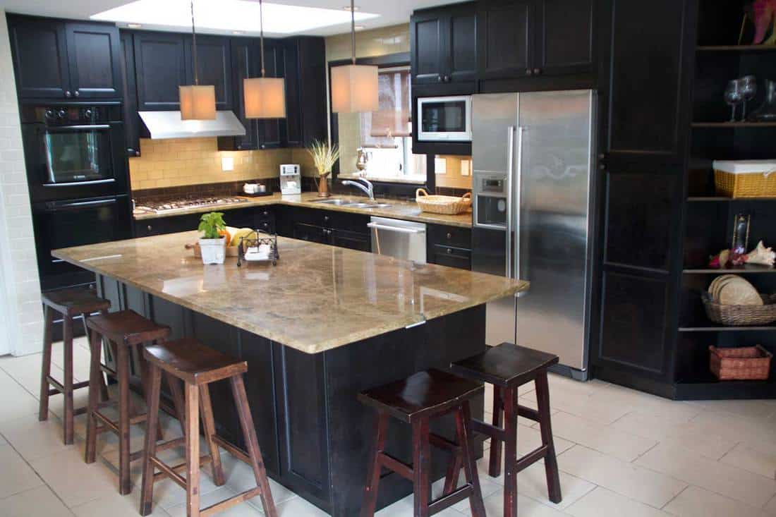 Modern kitchen with large island, stainless steel appliances, dark cabinets, tile floor, granite counters, bar stools, tiled backsplash in showcase condition