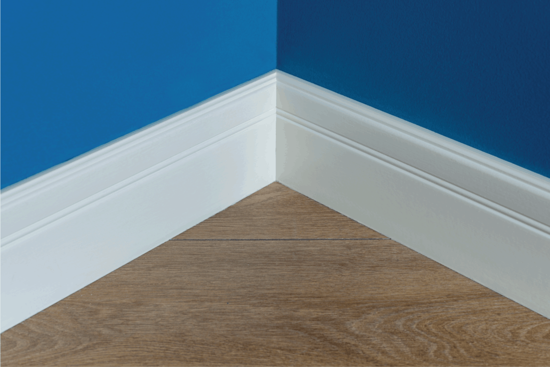 Moulding in the corner. Blue Matte Wall with laminate imitating oak texture