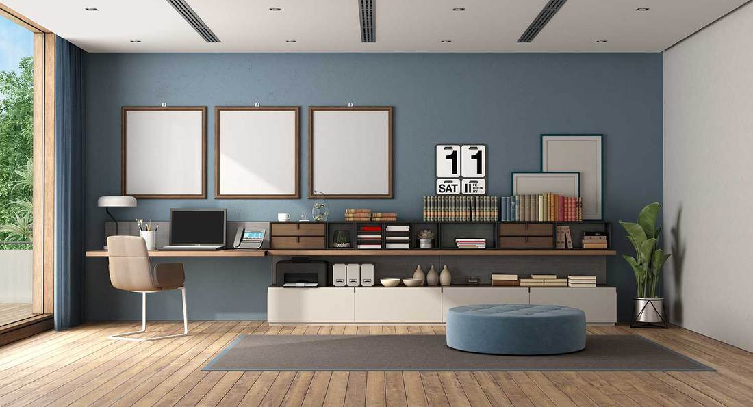Office room with desk and sideboard against blue wall