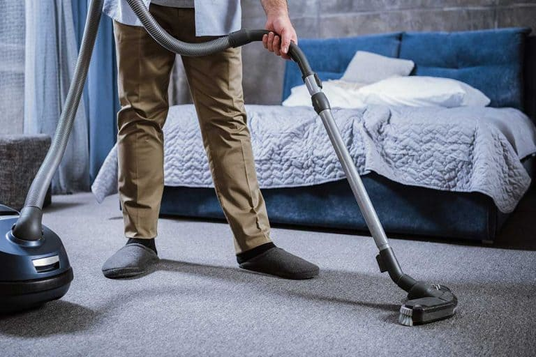Partial view of man with vacuum cleaner cleaning carpet in bedroom, How Often Should You Clean Your Bedroom?