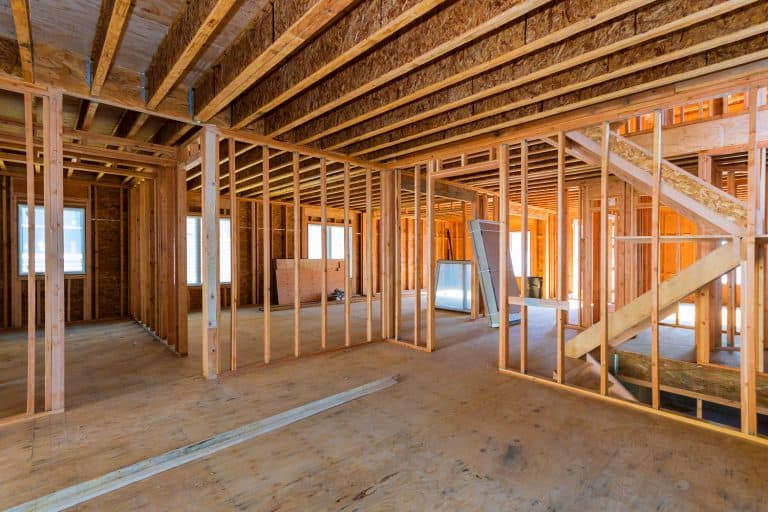 Photo of a house under construction with visible wood framing of the wall and ceiling, How To Attach Wood Framing To Concrete [4 Steps To Follow]