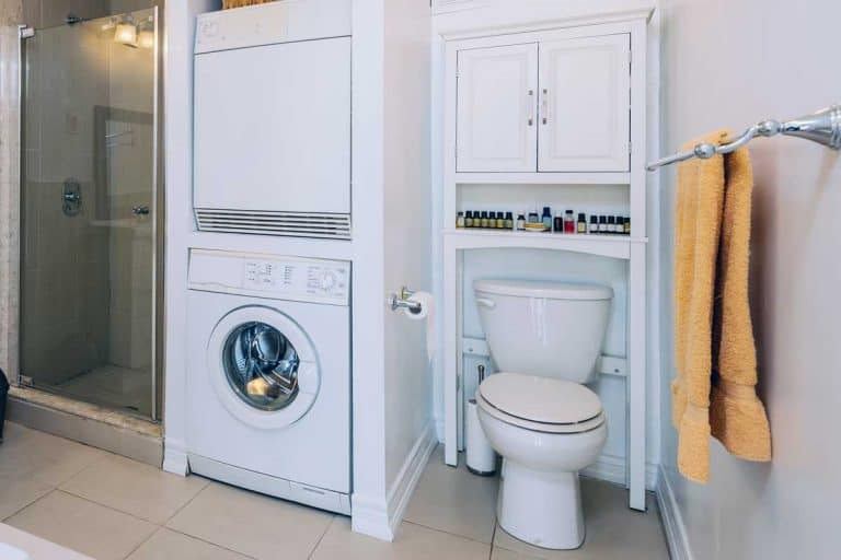 Rental condo main bathroom interior with washing machine, How High Should A Bathroom Cabinet Be Hung Over The Toilet?