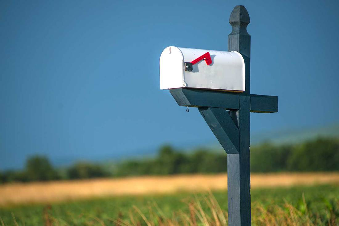Rural white mailbox with red flag on blue post astride road with field and blue sky in background