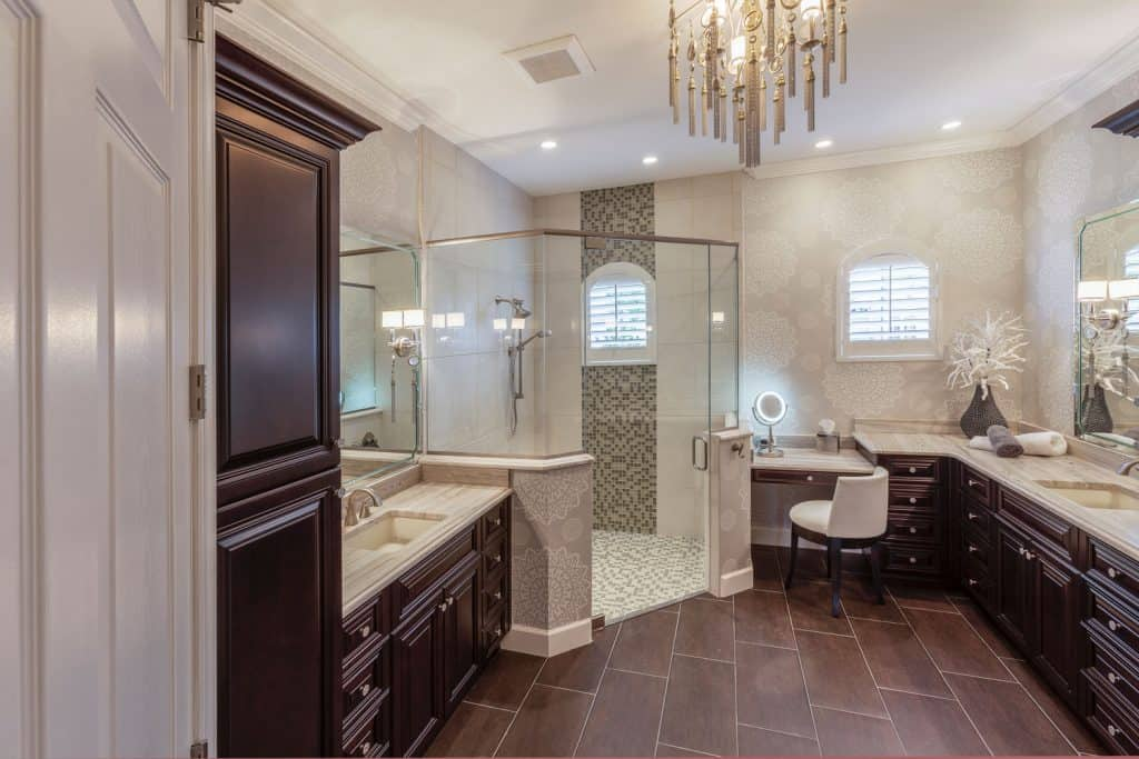 Rustic inspired bathroom with brown cabinetry, glass shower wall, and dangling chandelier