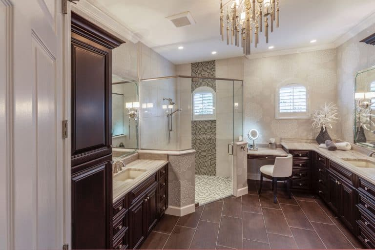 Rustic inspired bathroom with brown cabinetry, glass shower wall, and dangling chandelier, 11 Great Master Bathroom Cabinets Ideas
