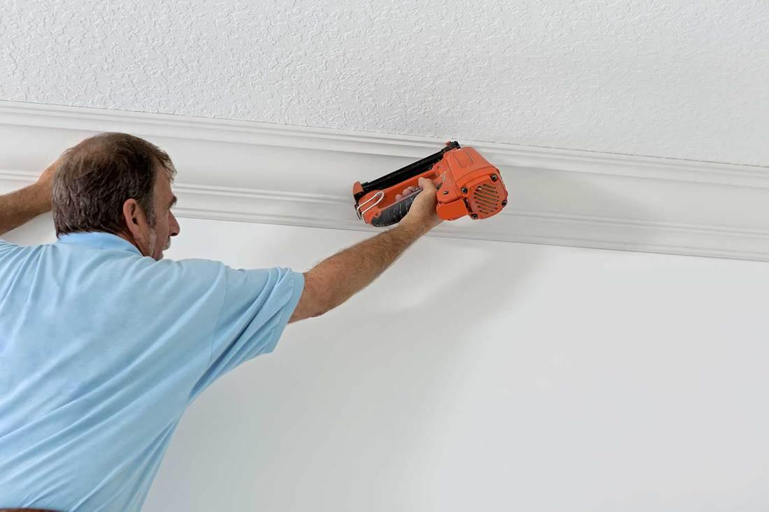 Senior carpenter installing crown molding