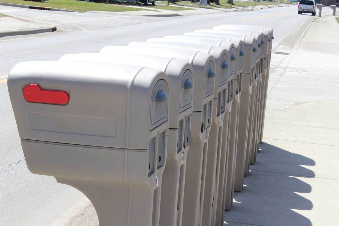 Several identical plastic mailboxes in a row at the edge of a street