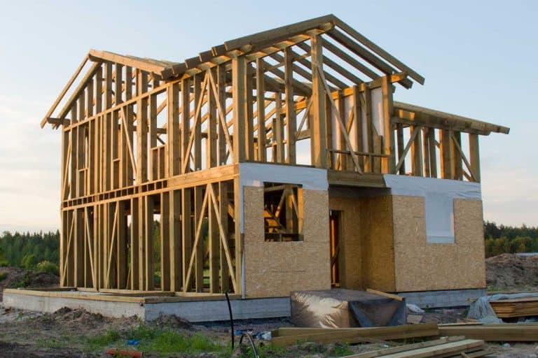Skeleton of a wooden two-story home surrounded by building materials, How Long Does Wood Framing Last?
