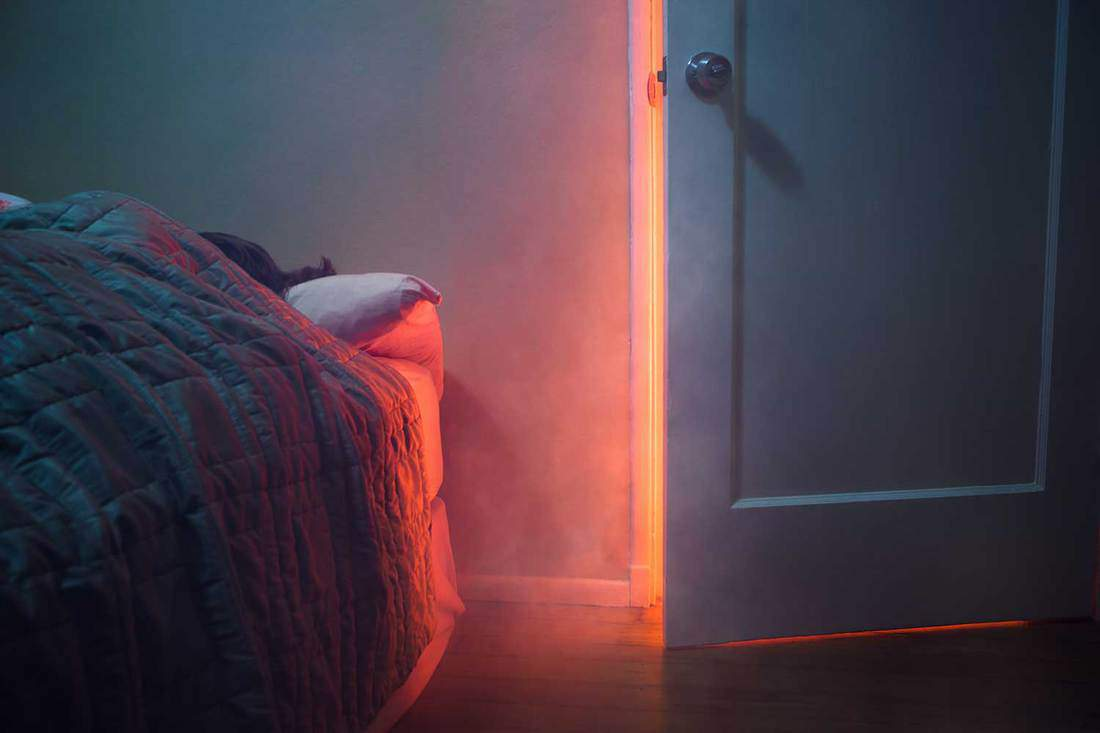 Smoke and light from a fire pour through a cracked bedroom door