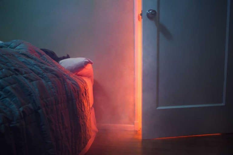 Smoke and light is visible through a slightly open bedroom door, Should You Close Bedroom Doors At Night? [And Should You Lock Them?]