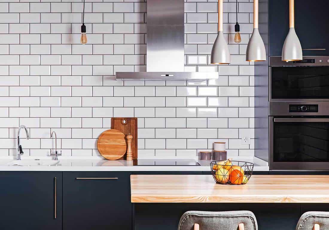 Spacious kitchen with white brick tile wall