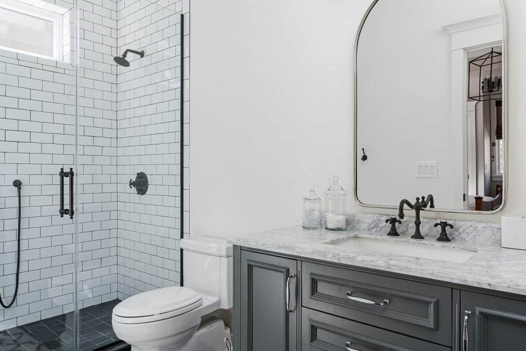 Stunning light dark bathroom design with gray cabinetry on the vanity, arched mirror, and a glass walled shower area