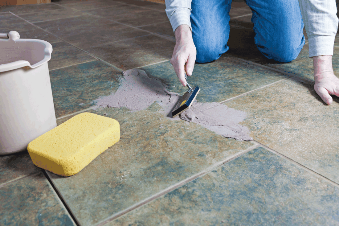 Tile Grout Repair, worker using trowel to spread grout