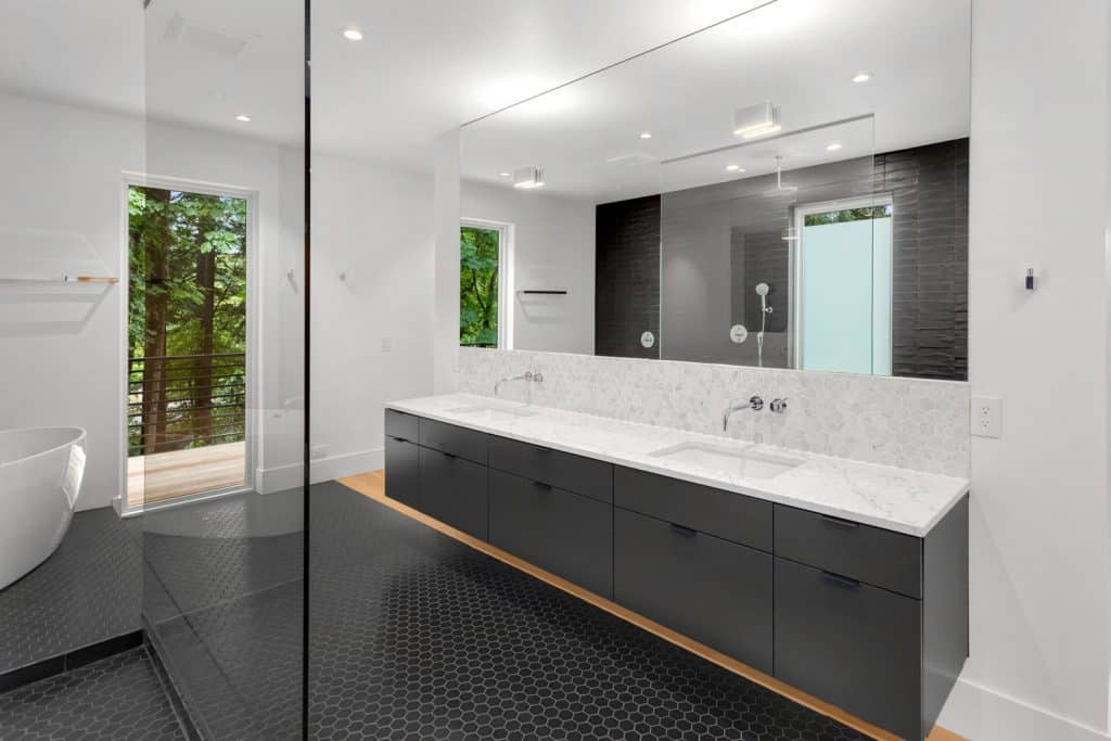 Ultra contemporary large bathroom with a huge mirror, gray painted cabinetry, and small dark tiles