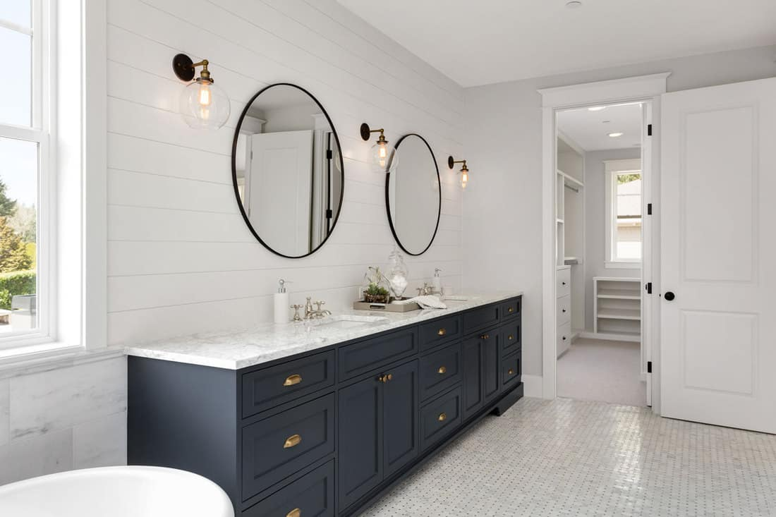 Ultra modern bathroom painted in white tiles, round mirrors, white gray cabinetry in the vanity section, and small lamps on the walls, What Wall Color Goes With A White Bathroom Floor?