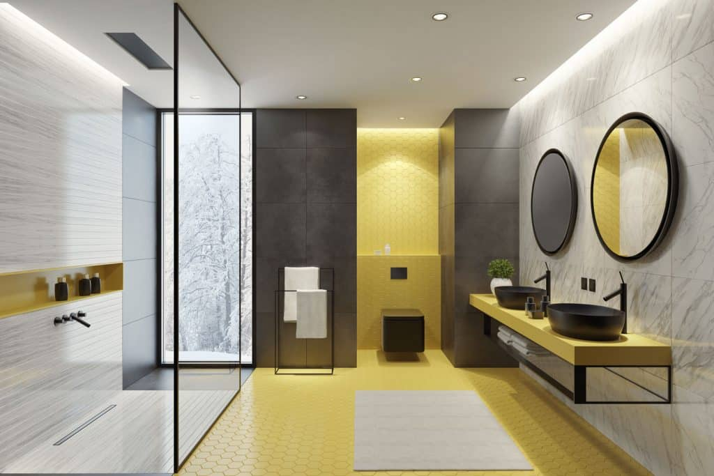 Ultra modern contemporary bathroom with a glass shower wall, yellow accent wall on the toilet area, and round mirrors on the vanity