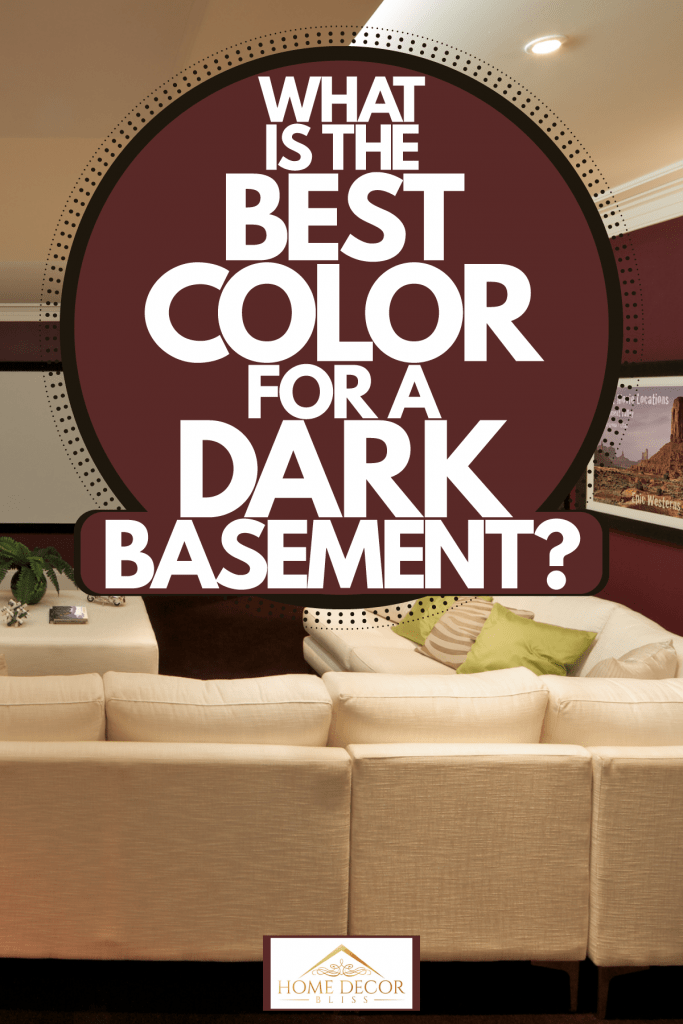 Interior of a contemporary basement with a white ceiling, red walls with huge landscape picture frames, and a huge beige colored sectional sofa, What Is The Best Color For A Dark Basement?
