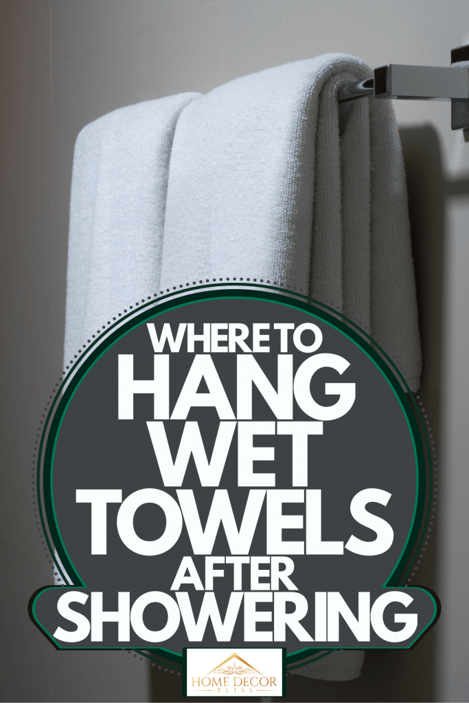 White towels hanged on a towel hanger inside an unlit bathroom, Where To Hang Wet Towels After Showering
