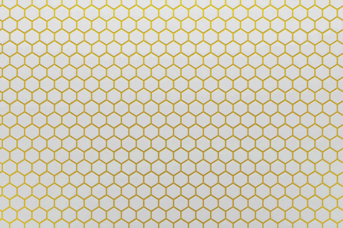 White ceramic hexagon tiles mosaic with gold grout in seams