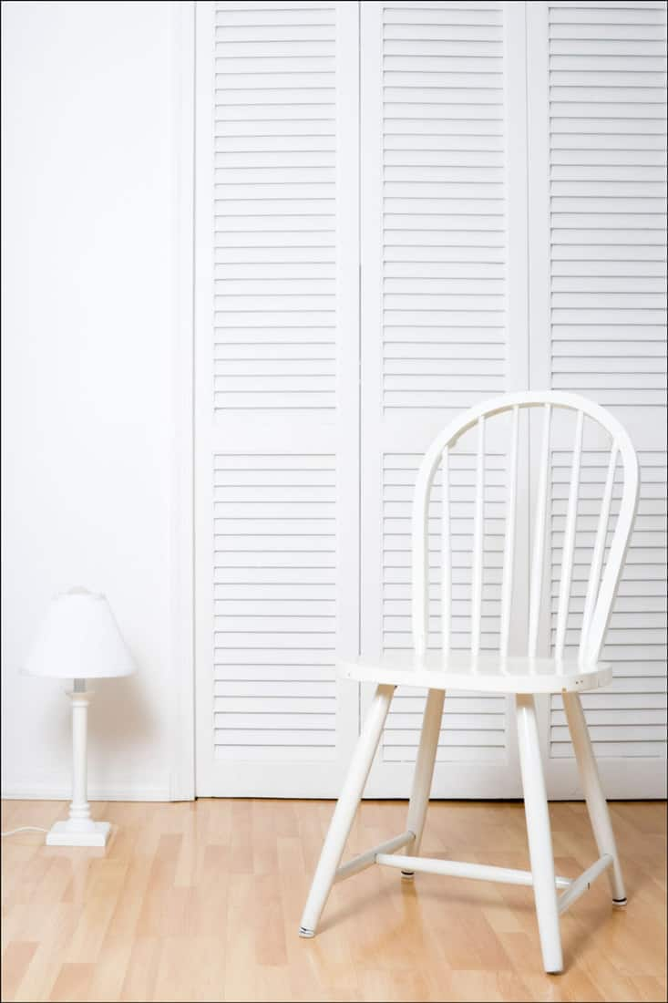 White chair, lamp and louvered doors, parquet floor. White chair has some small imperfections