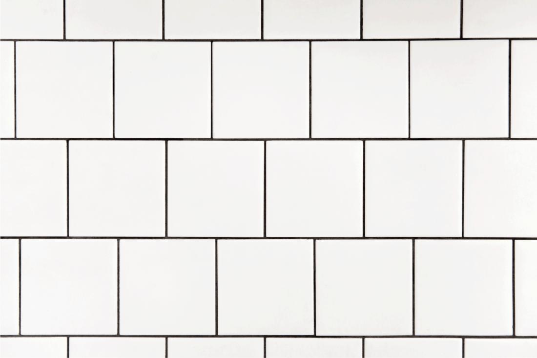White square ceramic tile with black seam, located horizontally