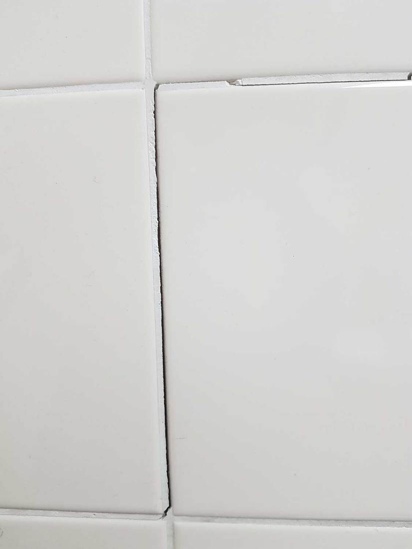 White wall tiles with a large crack