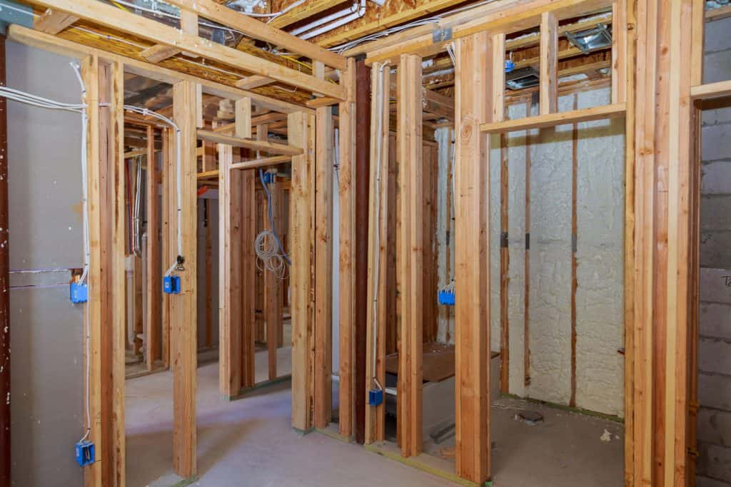 Wood framing under the basement with visible wiring and unfinished plastered cement