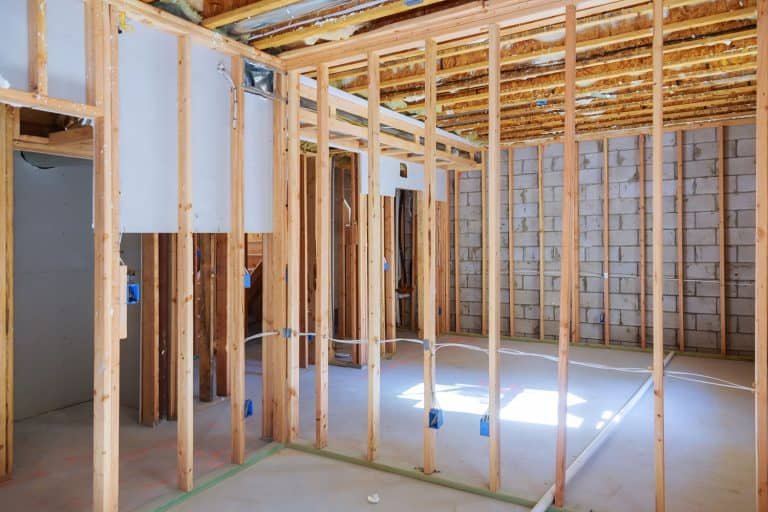 Wooden framing of a basement with visible wiring and unfinished plastered cement, What Wood To Use For Framing A Basement?