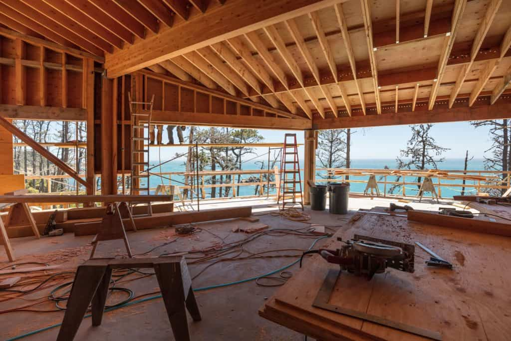 Wooden framing of a house with construction tools and wires scattered all over the room