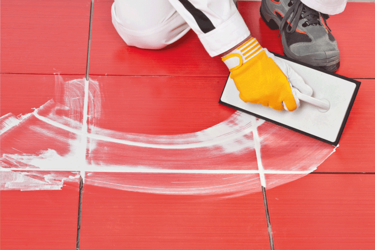 Worker with rubber trowel applying tile grout. 8 Bathroom Grout Alternatives You Should Know