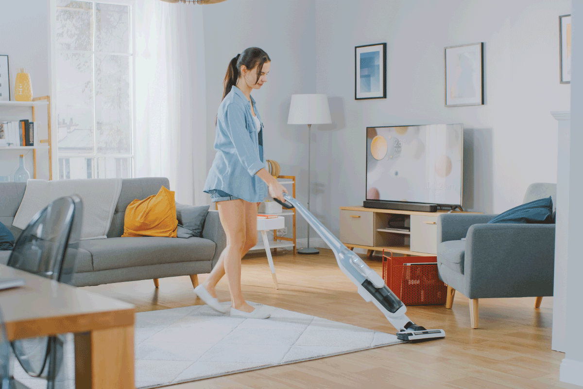 Young Beautiful Woman in Jeans Shirt and Shorts is Vacuum Cleaning a Carpet in a Bright Cozy Room at Home. Can You Use A Bissell Crosswave On Vinyl Or Laminate Flooring