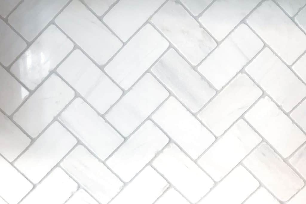 Zigzag patterned bathroom tiles with light gray grouting