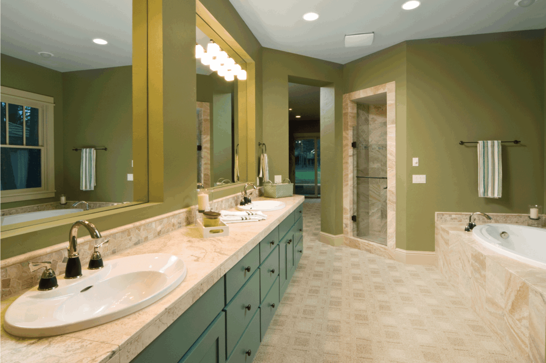 beautiful bathroom has double sink with mirrors and a sunken bathtub.