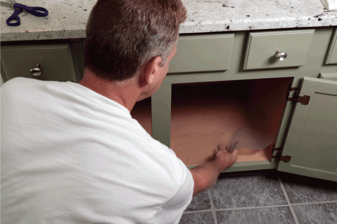 green painted wood cabinet a man lines the bottom of a bathroom cabinet with a plastic sheet