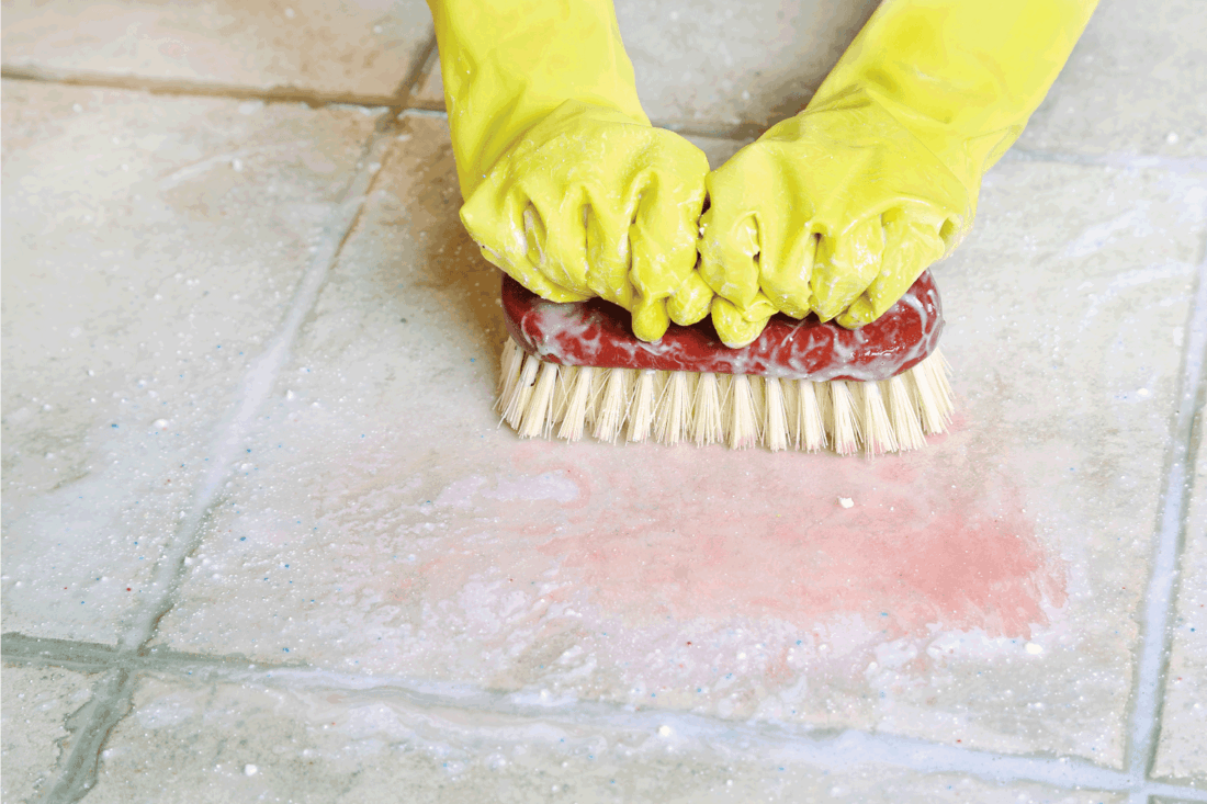 two hands in rubber gloves scrubbing down hard on tile and grout surface