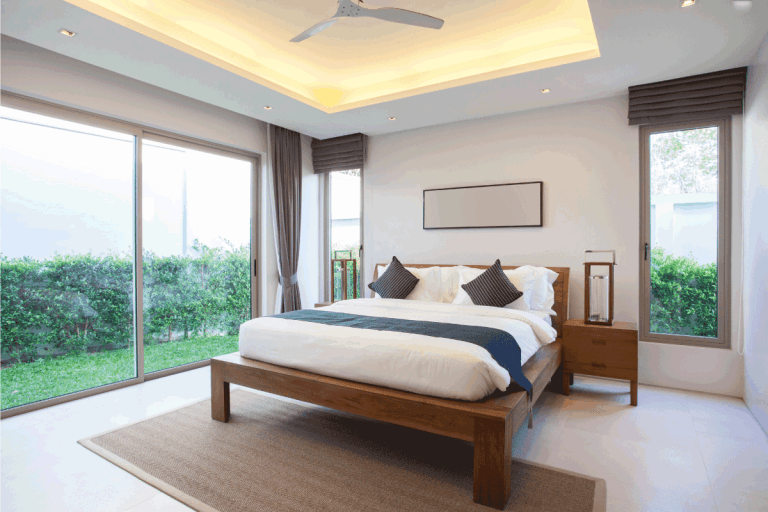 vibrant bedroom with glass sliding doors and windows, brown rug halfway through the end of the bed. Does A Bedroom Need A Rug [And How To Choose The Right One!]