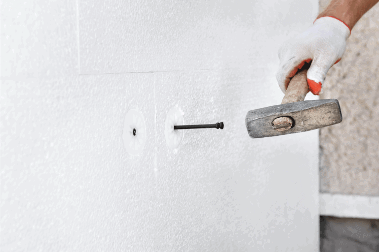 worker-is-using-a-hammer-for-dowels-that-fasten-drywall.-Nail-Pops-In-Drywall-Ceiling-Or-Walls---What-To-Do