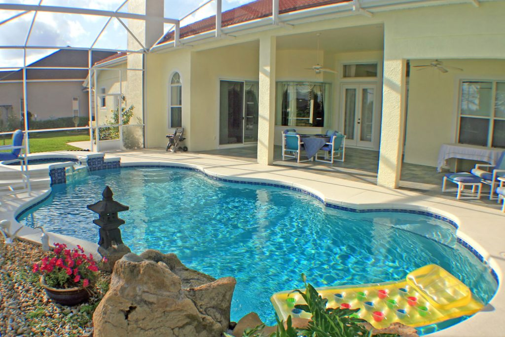 A beautiful screen lanai design with a huge pool and paired with beautiful landscaping on the back
