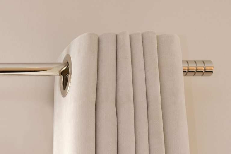 A beige colored curtain hanged on the stainless steel rod, How To Hang Curtains On A Sloped Ceiling In 5 Steps