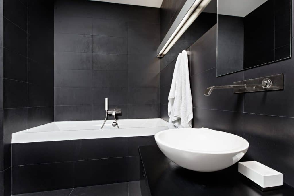 A black and white themed bathroom with dark countertop and a huge white ceramic bowl