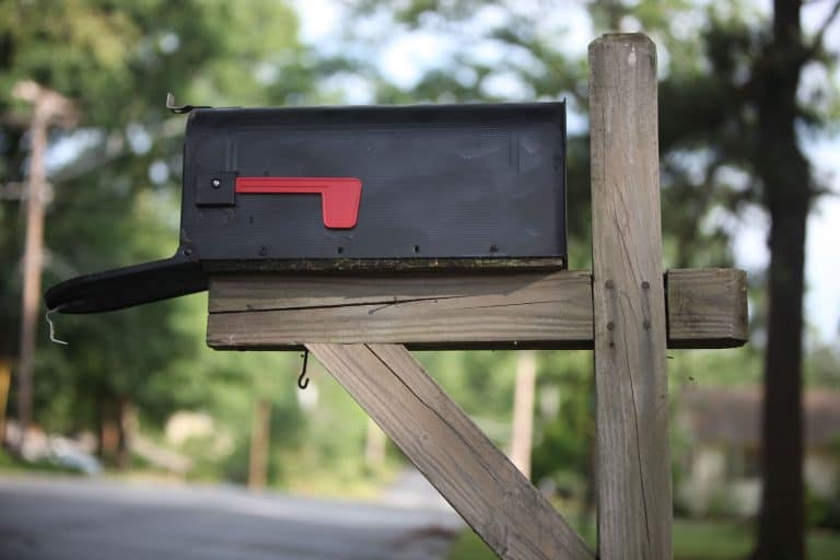 A black opened mailbox attached to a wooden frame, Are Mailboxes Waterproof?