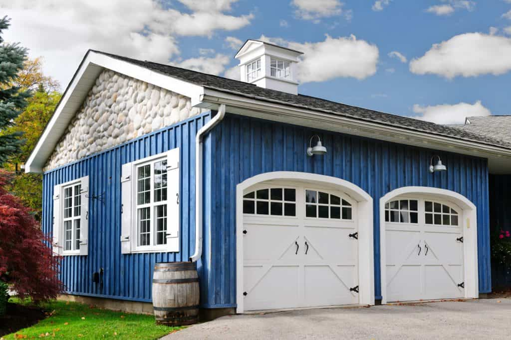 A blue colored wooden garage with white painted doors and small windows